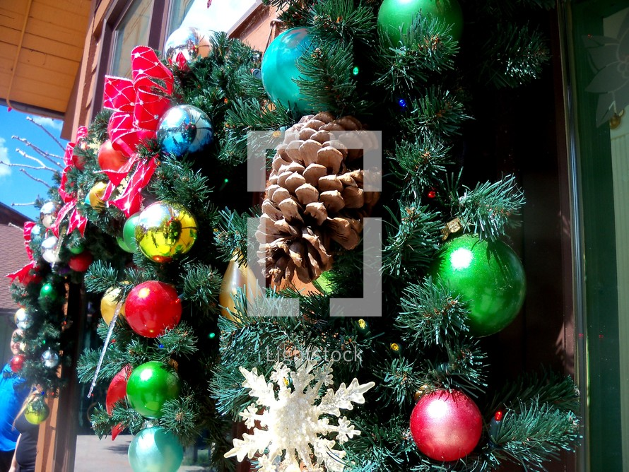 Christmas decorations adorning a holiday window wreath with snowflakes, red and green ornaments and a green evergreen adorned with red ribbons, pine cones and lively Christmas tree ornaments.