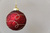 Red and gold hanging Christmas ornament against white background