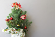 Small decorated Christmas tree with angel and presents against white / grey background