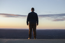 man looking at a valley with his back to the camera