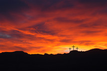 Silhouette of three crosses on a hill with a red sunrise sky