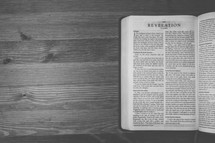 Bible on a wooden table open to the book of Revelation.