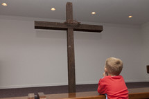 boy child looking at a cross