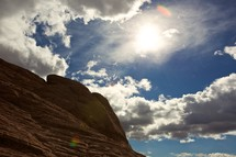 blue sky and white clouds over a red rock formation in Nevada