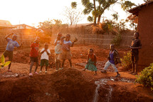 Children playing outdoors in red mud in Malawi, Africa.