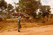 Man carrying a bundle of sticks along a dirt road.
