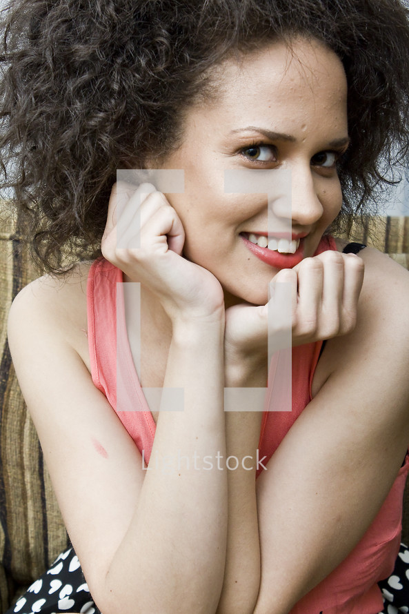 Smiling woman sitting with chin resting on her hands and elbows on her knees.