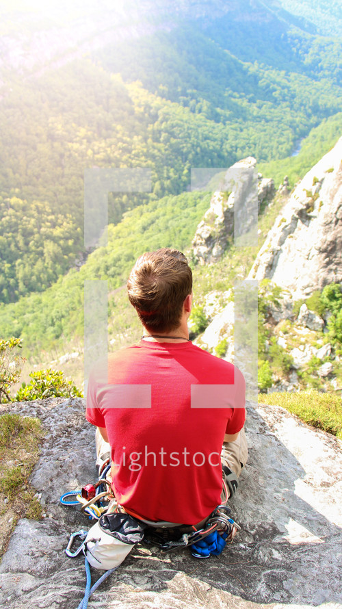 man siting on a rock on a mountain under sunlight