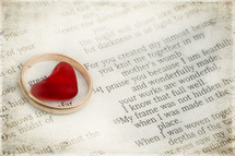 Heart in a gold wedding band on top of a Bible open to Psalm 139.