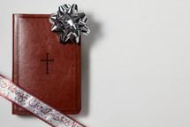 bow on the cover of a leather Bible on a white background