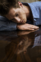 Man resting his head on hand lying on wood table top looking at reflection of his face.