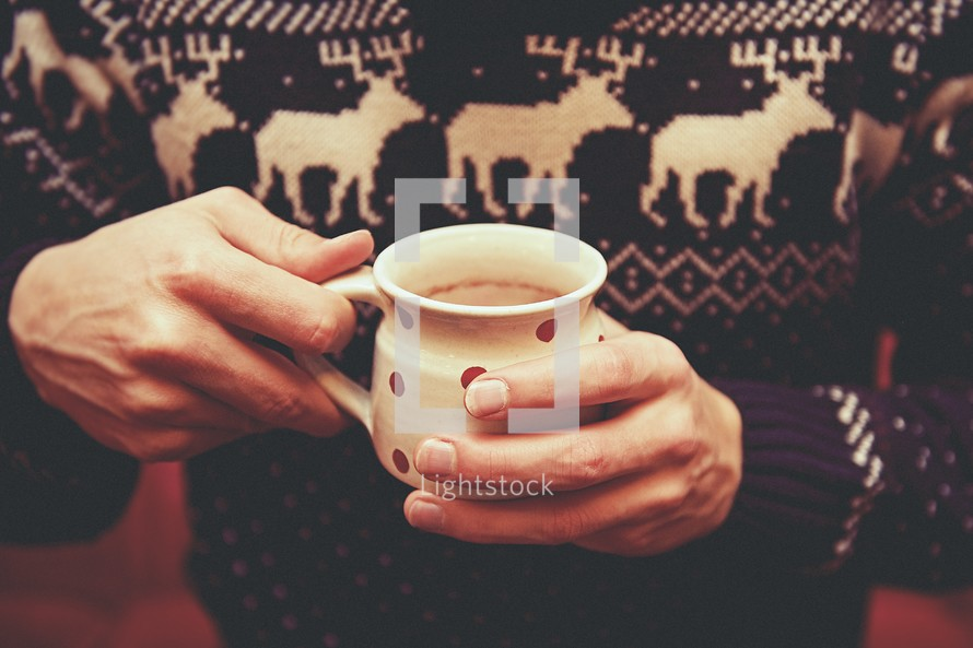 a man in a winter sweater holding hot chocolate