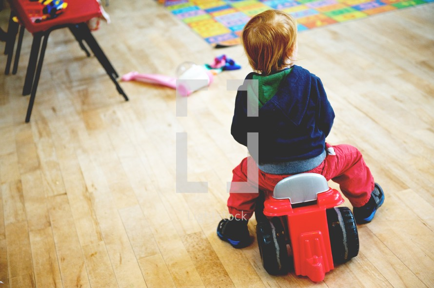 Young boy in a play room riding on a wheeled toy