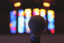Microphone in front of stained glass window.