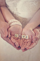 couple holding the word love in their hands