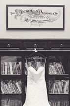 wedding dress hanging on a bookcase