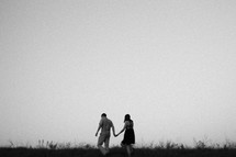 A man and woman walking through a field holding hands.