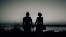 silhouette of a bride and groom standing on a shore