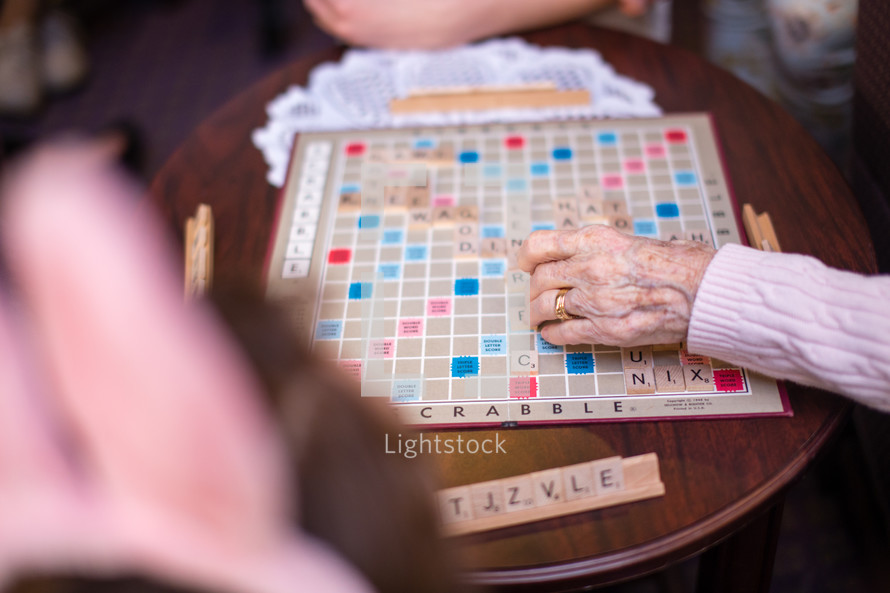 Elderly hands playing Scrabble on a wood table.