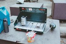 a tea pot on a camping stove
