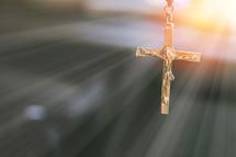 gold cross crucifix necklace in sunbeams
