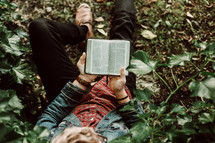 a young man sitting on the ground reading a Bible