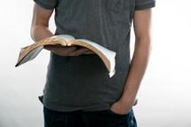 Teen holding an open Bible.