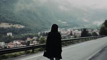 a woman walking down a foggy mountain road