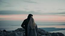 a couple kissing on a rocky shore