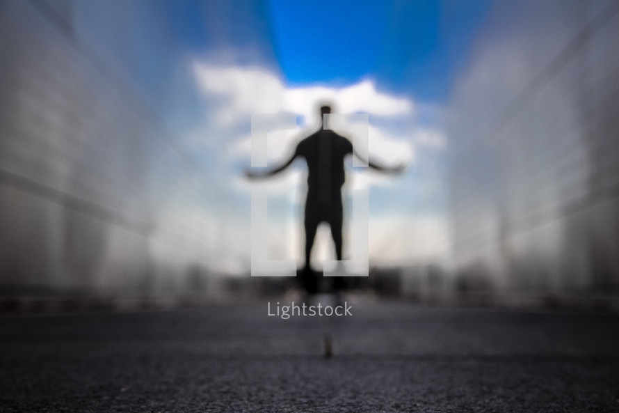 blurry silhouette of a man with outstretched arms