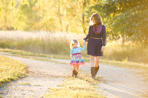 A mother and daughter walking holding hands outdoors