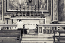 man kneeling in prayer at an altar