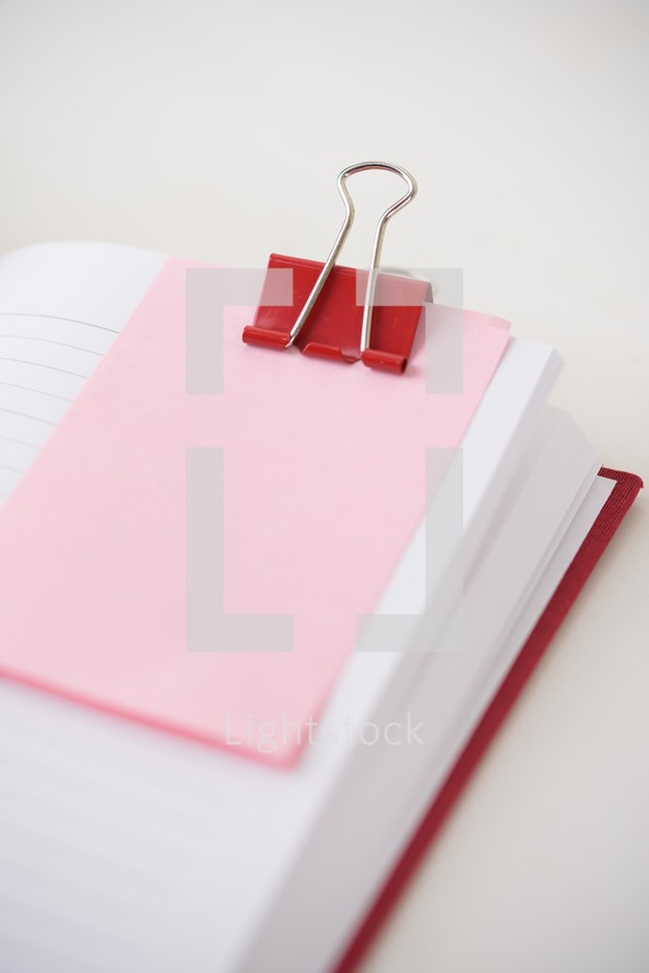 red clip and pink paper on blank journal pages