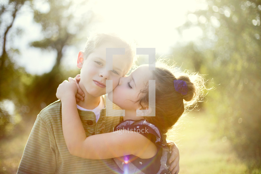 A sister hugging and kissing big brother on the cheek