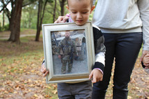 Boy standing in the woods with his mother, holding a framed photo of his soldier father.