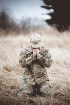serviceman kneeling in prayer in a field