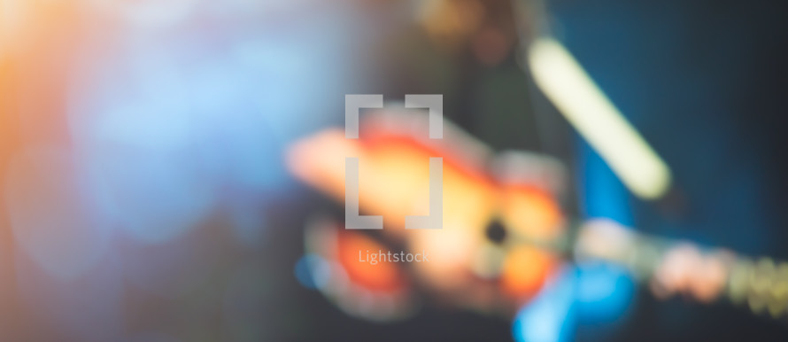 blurry image of a man on stage playing a guitar