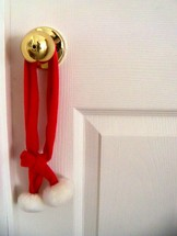 Christmas decor hung on a doorknob to decorate a home for Christmas to add warmth, color and fun for the holidays.
