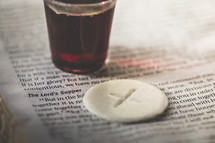 communion cup and wafer on the pages of a Bible