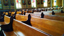 Rows of beautiful wooden church pews sit empty in a large church filled with stained glass windows and ornate architecture.