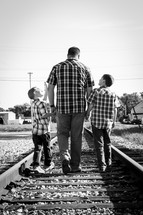 father walking holding hands with his sons on railroad tracks