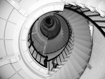 A winding spiral staircase inside of a Light House in Central Florida. To climb these steps takes some strength and stamina as well as determination as these steps climb the length of this light house overlooking the ocean, serving as a beacon of light to the ships at sea in a time of storm.
