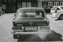 a couple in an old Mercedes driving away