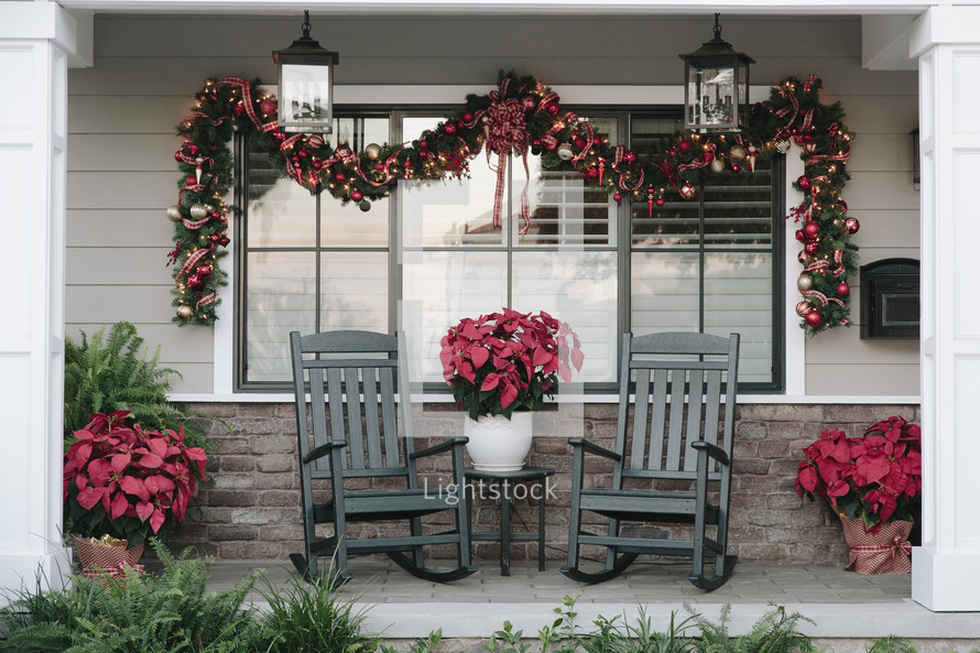 A porch with rocking chairs decorated for Christmas.