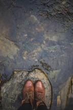 Boots on a rock in a stream.