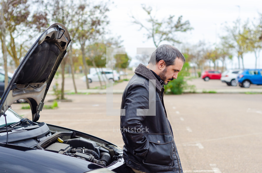 a man standing next to a car with engine trouble