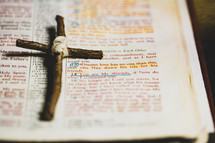 """Rustic handmade cross lying by John 15:13 scripture in Bible that says, """"Greater love has no one than this, that one lay down his life for his friends."""""""