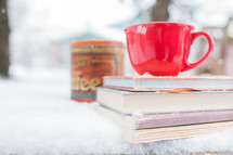 a red mug on a stack of books on a table outdoors in the snow