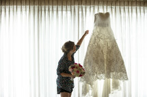 wedding gown hanging in a window