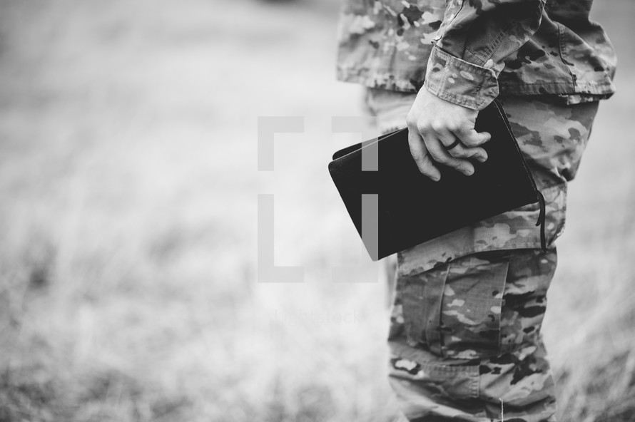 solider holding a Bible